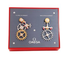 Lot #5683 – Omega Moving Display Co-Axial Escapement VS Swiss Lever Escapement Machine Omega Omega